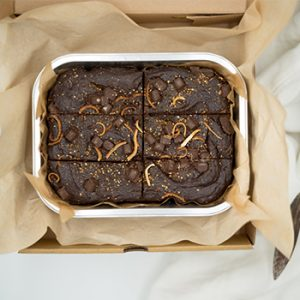 orange flavored chocolate brownie in a tray and box