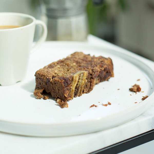 one slice of banana loaf with a cup of coffee on a plate